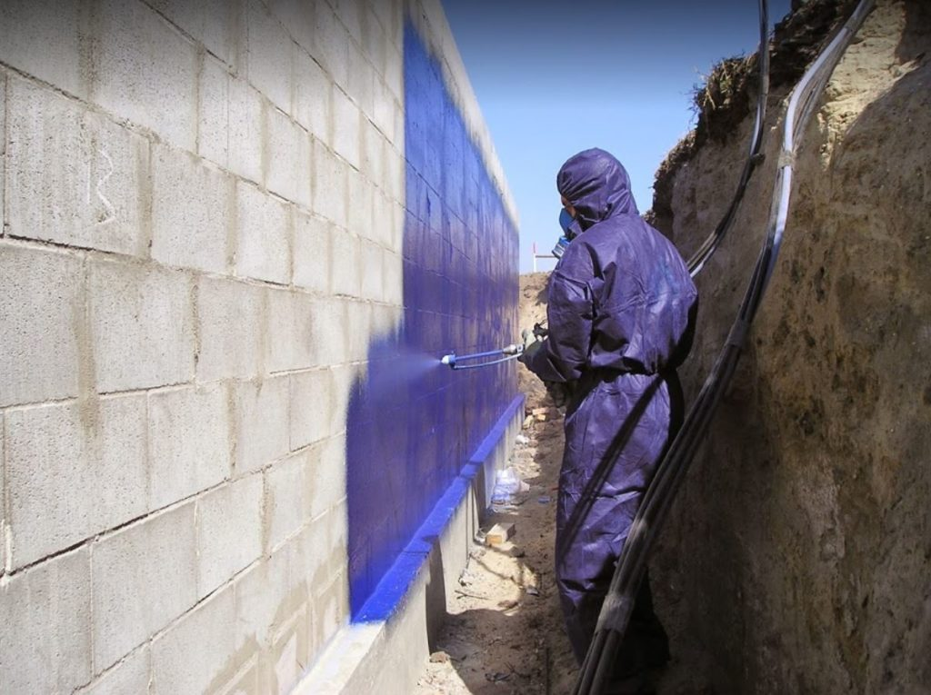 spray gun applicator waterproofing retaining wall side of house construction spray gun blue Elaston Tufflon polyurea