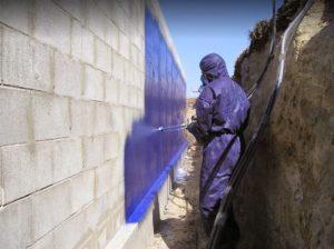 spray gun applicator waterproofing retaining wall side of house construction spray gun blue Elaston Tufflon polyurea