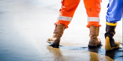 Workmen boots on concrete floor flooring image